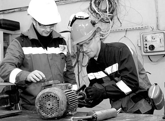 Старший мастер Константин Жуковской обучает студента ТПУ Юрия Мартемьянова ремонту электродвигателя