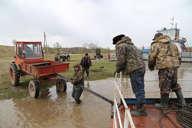 Уровень воды в Чулыме падает, и даже катера-буксиры порой садятся на мель. Помогают отчалить от берега трактор и рабочие
