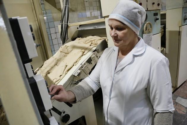 Галина Качкина на «Томском кондитере» трудится уже 27 лет. Ее фронт работы – контролировать процесс вальцовки теста. Оно складывается в 32 слоя, а затем, проходя через вальцы, приобретает нужную толщину. Для крекера, например, это два миллиметра, для затяжного печенья – четыре. Необходимые режимы задаются автоматически
