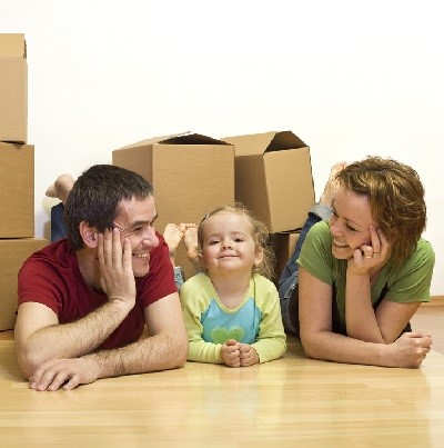 Happy couple with a kid in their new home laying on the floor with cardboard boxes around