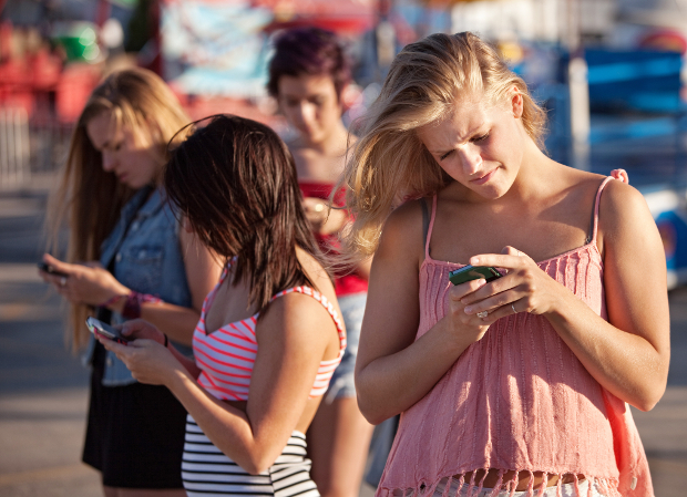 Four female teenagers using their phones outside